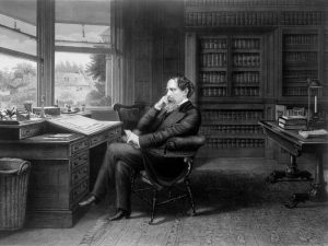 A black and white portrait of Charles Dickens pondering at his writing desk in his study.
