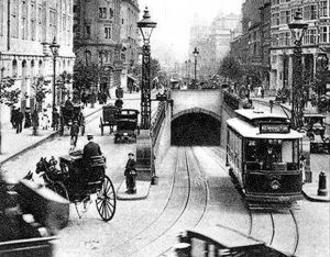 A tram exiting Kingsway Tram Tunnel onto the heavily-trafficked street above.