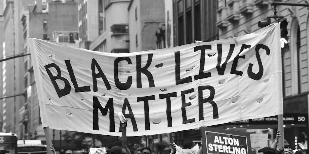 A black and white photo of a Black Lives Matter banner held up at a protest.